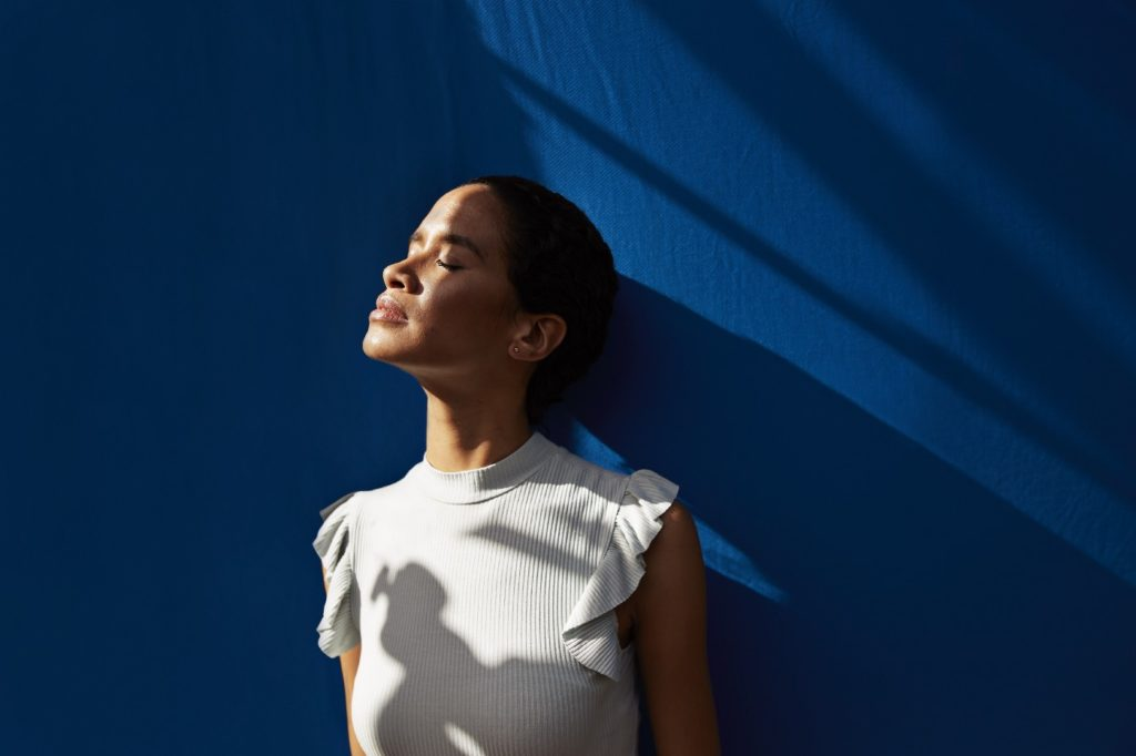 Woman looking up with her eyes closed against a blue background