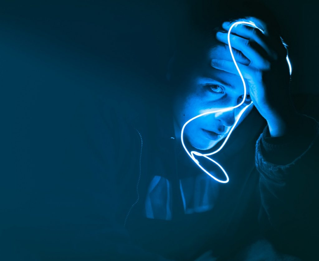 Person's face looking concerned glowing blue with a dark background