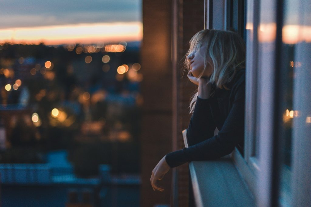 Woman leaning on a window ledge with a city in the background, looking forlorn